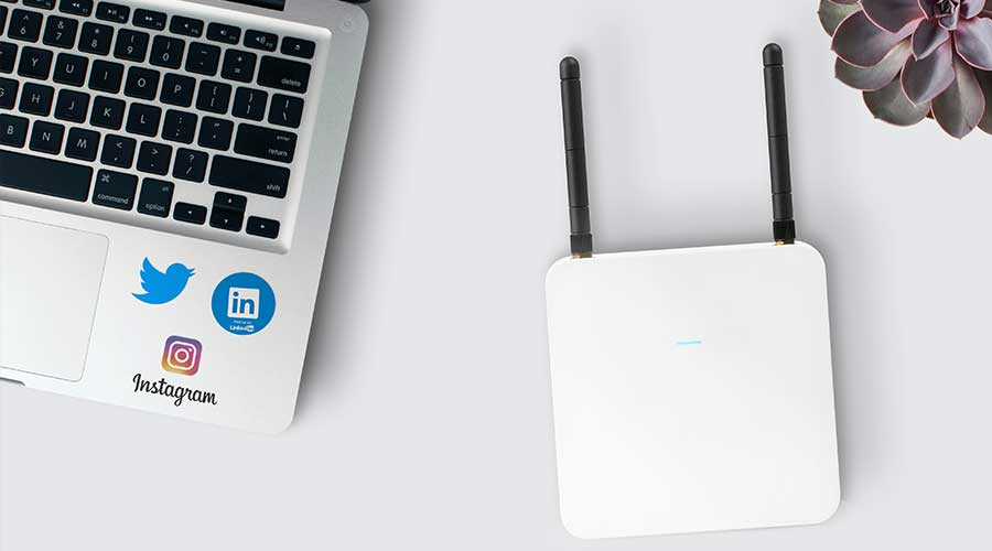 A wifi extender next to a laptop. Buy one with one of the best routers under 100.